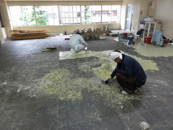 電動工具と手作業で、床に張り付いたPタイルをはがしている様子