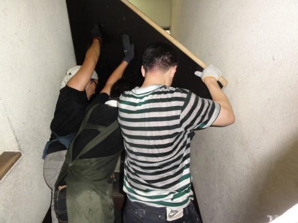 裏階段を汗だくで、8人で運び上げしている様子