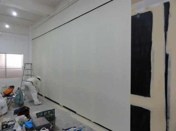 壁紙が貼れるように、やすりをかけ、紙のシートを下地に貼っている様子。この上に壁紙を貼ります。