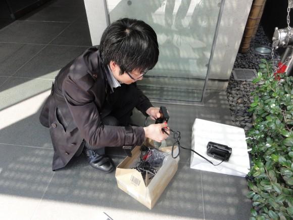 ▲座り込んで箱からCEREVO LIVEBOXを取り出す長谷川さん